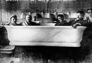 Workers sitting in Taft bathtub before installation.